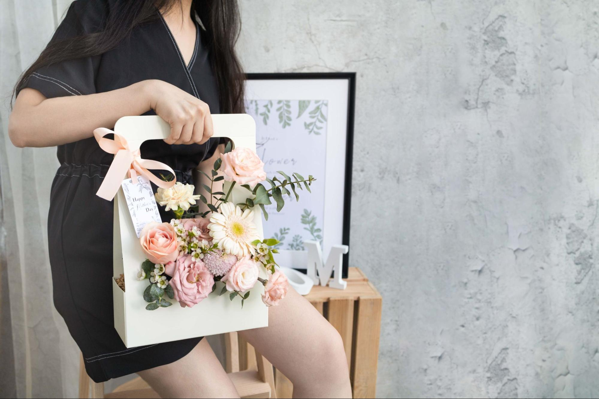A woman holds a stunning box filled with flowers online Singapore.
